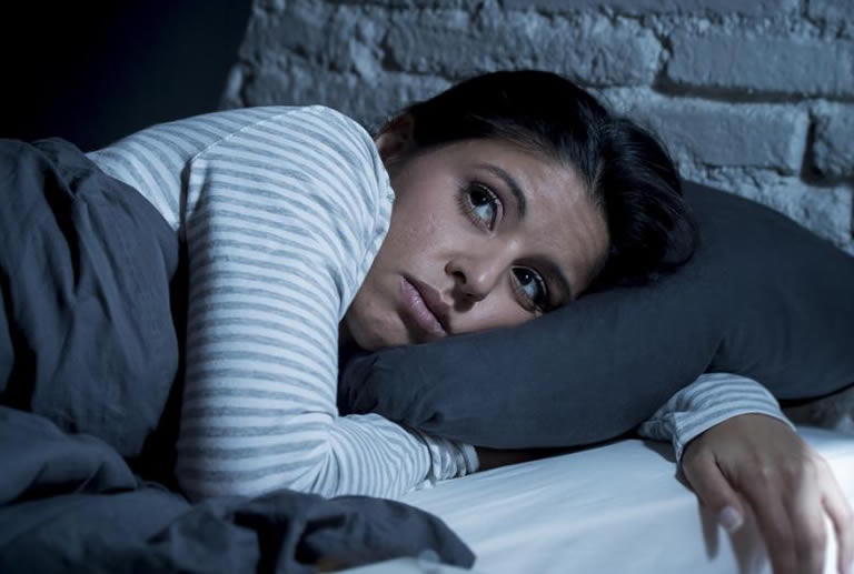 Woman in bed not wanting to lucid dream