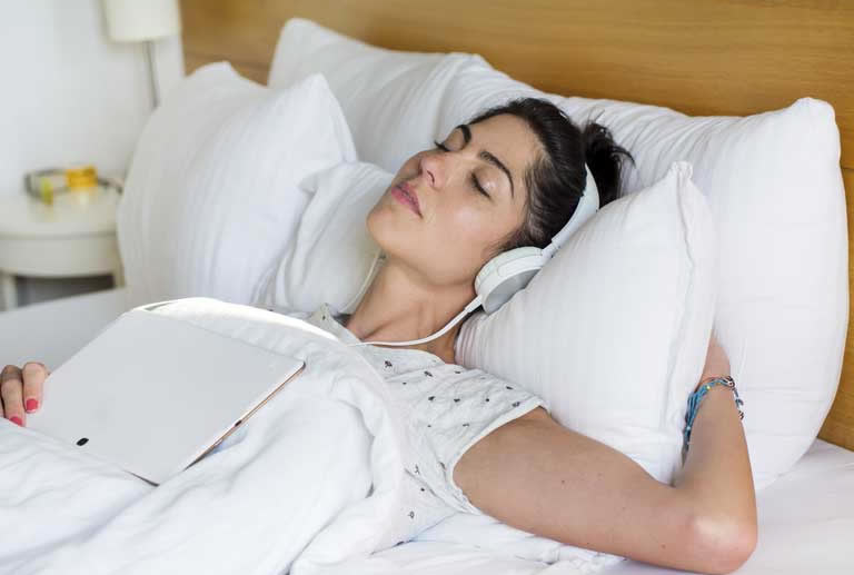 Woman listening to lucid dreaming music while sleeping